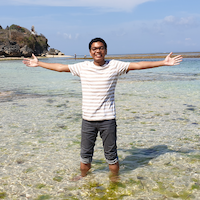 Teuku has his arms raised, a big smile on his face, as he stands in a beautiful blue-green ocean
