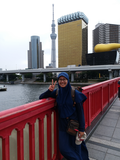 Ainun is smiling and giving the peace symbol in front of the landscape of a city on the water